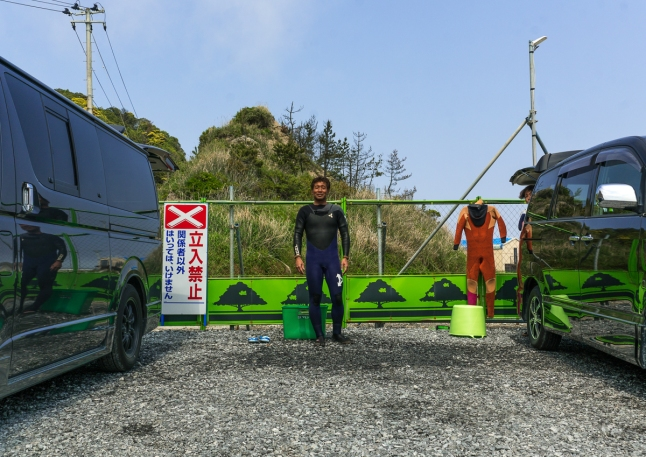 Japanese surfer in the contaminated area in front of a authorized entry prohibited sign , Fukushima prefecture, Tairatoyoma beach, Japan